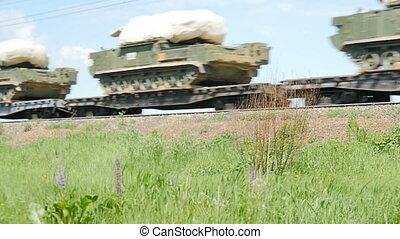Military equipment is transported on platforms by rail....