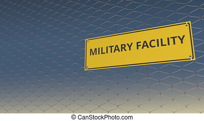 MILITARY FACILITY sign an a mesh wire fence against blue...