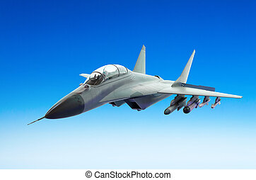 Military fighter fly above a blue sky.