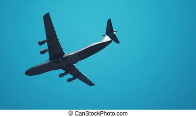 Military freighter plane flying overhead in blue sky - Close...