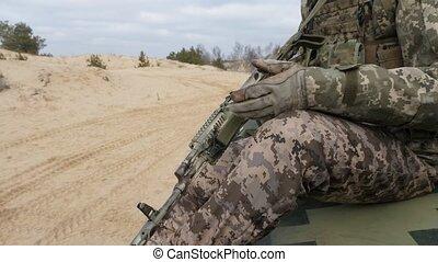 Military guy in khaki uniform with AK-74 riding on a modern...