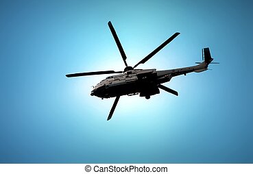 Military helicopter flying under blue sky