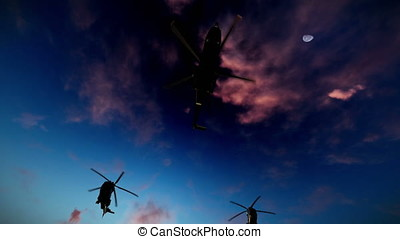 Military helicopter formation flying at sunset