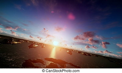 Military helicopters cruising above ocean, sunrise