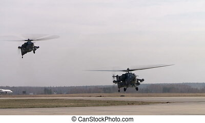 View of military helicopters fly over airstrip