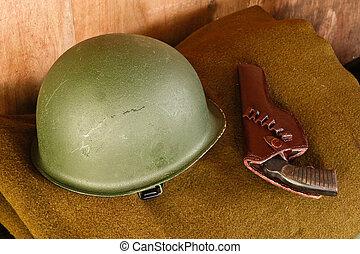 Military helmet and revolver on blanket