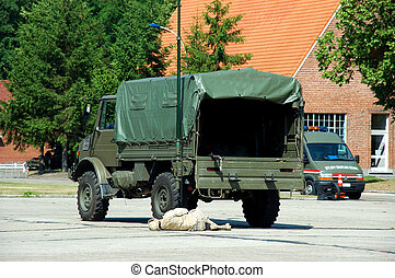 military intervention. soldier in action. War concept. Injured victim in front of truck.