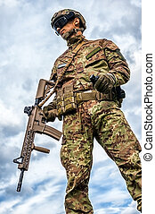 military man holding automatic rifle and hand grenade