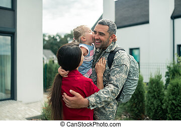 Military man hugging his wife and daughter after returning home
