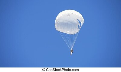 Military man in a white uniform landing on a white round ...