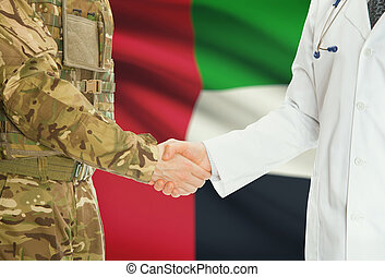 Military man in uniform and doctor shaking hands with national flag on background - United Arab Emirates