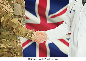 Military man in uniform and doctor shaking hands with national flag on background - United Kingdom