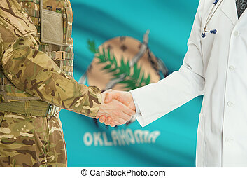 Military man in uniform and doctor shaking hands with US states flags on background - Oklahoma