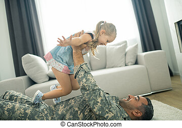 Military man lying on the floor and lifting his cute lovely daughter