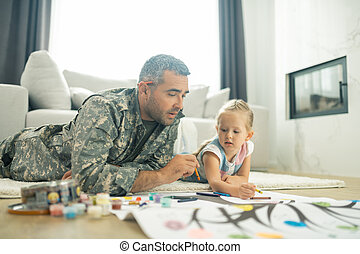 Military man painting family tree with his cute daughter