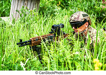 Military man sniper with automatic rifle with a telescopic sight lies in grass in forest