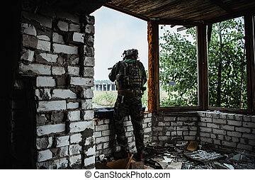 Military man with gun case takes out an assault rifle in destroyed city. Military and rescue operation concept.