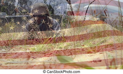 Military man with gun crawling and the American flag