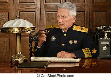 Military mature general - Elderly military sits at a table...