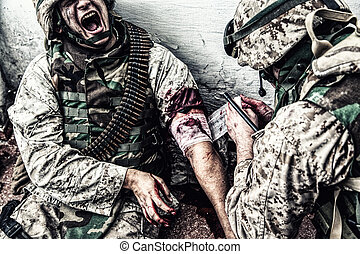 Marine wounded in shoulder, suffering of pain and screaming while receiving medical aid from comrade. Military medic apply pressure bandage to casualty, binding gunshot wound, trying stop bleeding