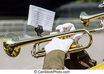 military musician blowing his gold trumpet