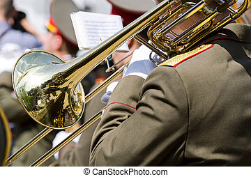 military musician playing gold trombone on parade