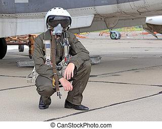 military pilot in a helmet near the aircraft