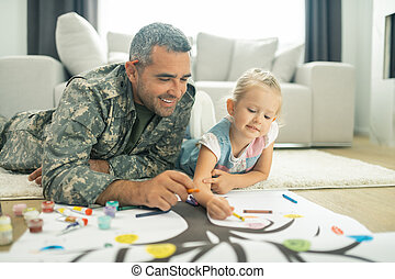Military servant and his daughter painting family tree together