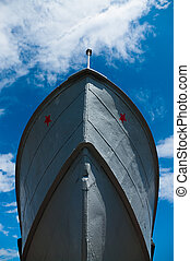 Military ship`s prow on the blue sky background