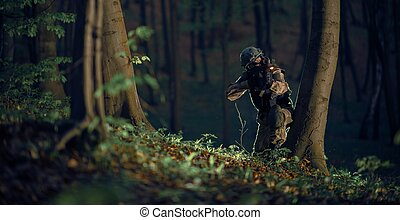 Military Soldier in Action at Night in the Forest Area. ...