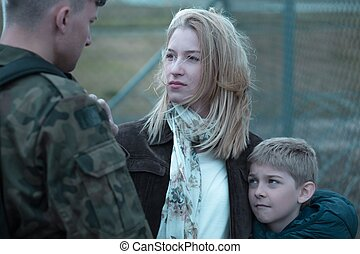 Military soldier saying goodbye to wife and son