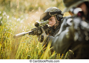 military soldier shooting an assault rifle - military sniper...