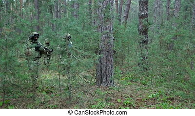 Military special forces moving in the forest. Soldiers in...