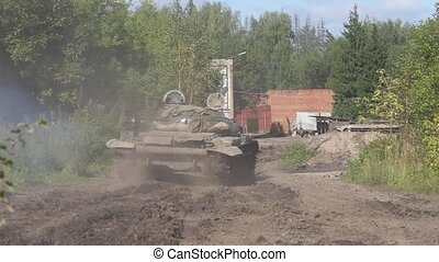 Military tank driving on road on background destroyed...