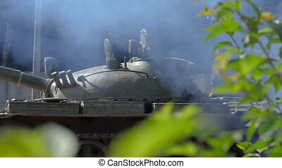 Military tank on smoke background standing on war field slow...