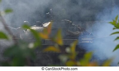 Military tank with smoke moving on battle field. Armored...
