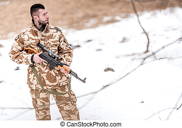 Military trooper, ranger, holding a machine gun on the battlefield