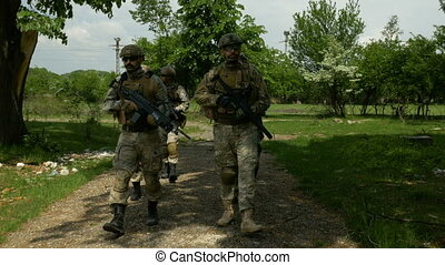 Military unit walking and patrolling near abandoned building...