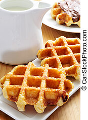 milk and waffles - a pot with milk and some waffles in a ...