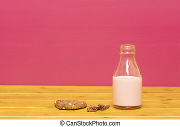 Milk bottle half full of strawberry milkshake with half-eaten cookie