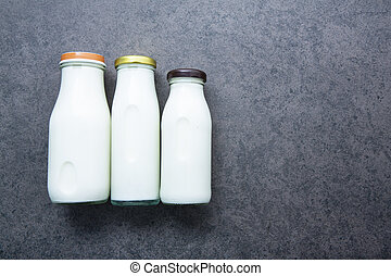 Milk bottle on dark stone background. Top view with copy space.