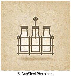 milk bottles in basket on old background