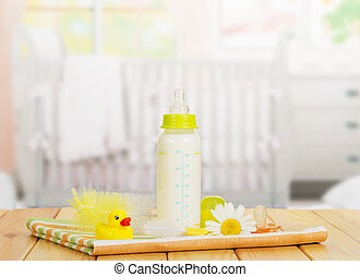 Milk, brush for washing bottles, pacifier  on  table in  nursery.
