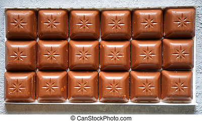 Milk chocolate bar with nuts close up. Fast carbohydrates.