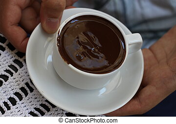 milk chocolate cup hold in human hands