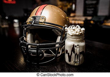 Milk chocolate drink with marshmallow on the background of a football helmet
