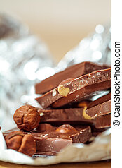 Milk chocolate pieces with nuts on foil