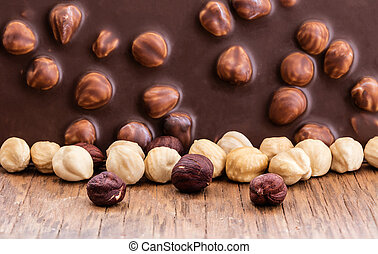 milk chocolate with hazelnuts on a wooden background