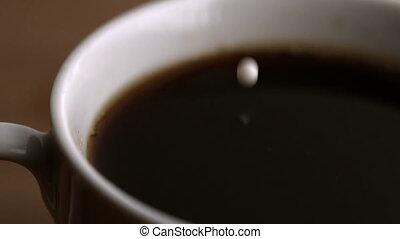 Milk drop falling into cup of coffee - Milk drop falling...