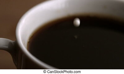Milk drop falling into cup of coffee